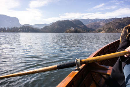 Young woman using paddle on a wooden boat - Lake Bled Slovenia rowing on wooden boats Banco de Imagens