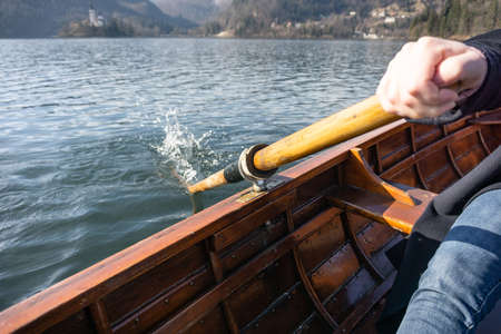Young woman using paddle on a wooden boat with island Bled behind it - Lake Bled Slovenia rowing on wooden boats