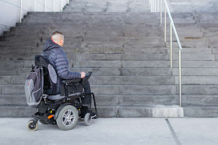 Disabled man on an electric wheelchair who cant get up the stairs Stockfoto