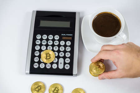 Golden Bitcoin held by hand on black calculator next to coffee, cryptocurrency concept Фото со стока - 120902097