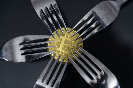 Bitcoin getting New Hard Fork Change, Physical Golden Crytocurrency Coin under forks Stock Photo
