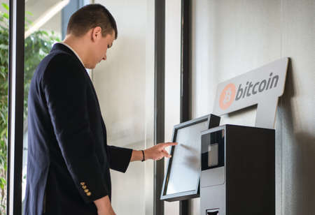 Young businessman buying cryptocurrency on ATM machine for buying and selling cryptocurrency. Stock Photo