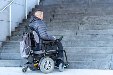 young disabled man in a electric wheelchair in front of stairs