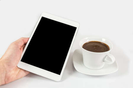 Digital tablet in one hand, on a white background next to coffee mug full of coffee, isolated