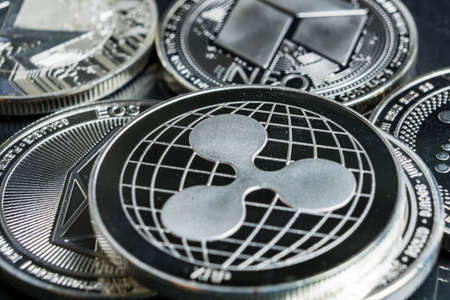 Ripple cryptocurrency physical coin surrounded with variety of other crypto altcoins.