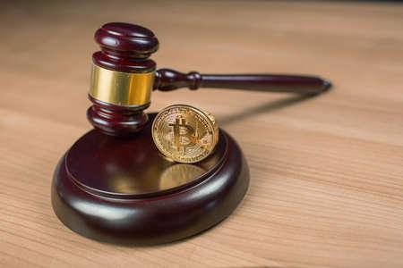 Bitcoin-Regulierung. BTC-Kryptowährungsmünze und Richterhammer auf einem Schreibtisch. Verbotenes Währungs- oder Strafverfolgungskonzept.