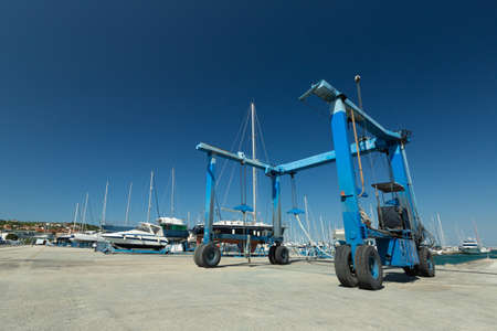 Blue lifting crane for elevating boat and maintenance machine at harbor dock Imagens