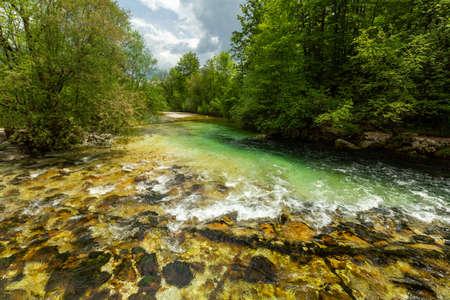 Colorful spring panorama of Sava bohinjka river at the Bohinj Lake village Ukanc. Picturesque moning scene in the Triglav National Park, Julian Alps.