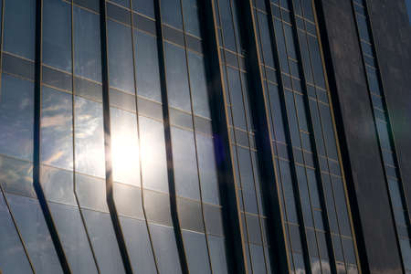 closeup of a modern window glass building with sun reflecting in it
