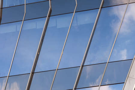 closeup of a modern window glass building with blue sky and clouds reflecting in it Stock Photo - 124690046