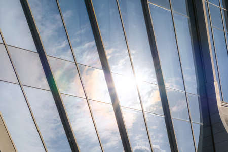 closeup of a modern window glass building with sun and blue sky reflecting in it Stock Photo