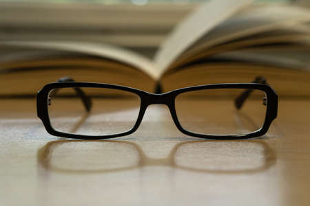Photo of glasses and opened book behind them, reading concept