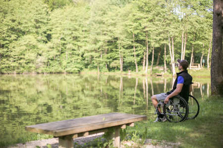 Happy and young disabled or handicapped man sitting on a wheelchair looking at beautiful lake in nature.