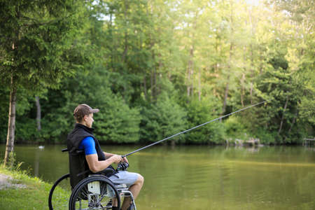 Happy and young disabled or handicapped man fishing at a lake in nature. Popular sport for paraplegics. 版權商用圖片