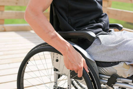 Disabled young athletic man on a wheelchair holding and turning wheels with hand engage in sports Banque d'images