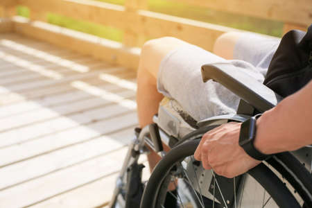 Disabled young athletic man on a wheelchair holding and turning wheels with hand engage in sports Imagens