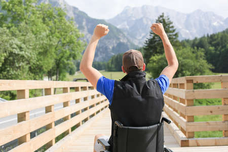 Disabled young man on a wheelchair in nature feeling excited and full of optimism like a winner