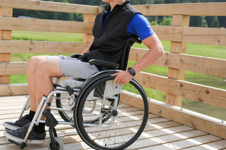 Disabled young man on a wheelchair holding and turning wheels with hand