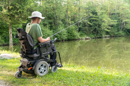 Happy man in a electric wheelchair fishing at the beautiful pond in natue on a sunny day Imagens