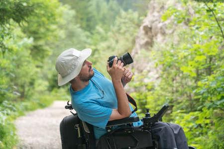 man on electric wheelchair using mirrorless camera nature, enjoying freedom and doing art Zdjęcie Seryjne