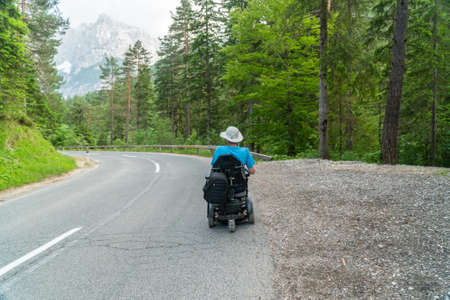 disabled person in an electric wheelchair driving on the street, road Standard-Bild