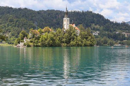 Lake Bled Slovenia. Beautiful mountain lake in summer with small Church on an island with castle on cliff and european alps in the background.