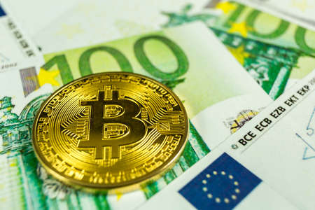 Crypto currency concept - A bitcoin with euro bills