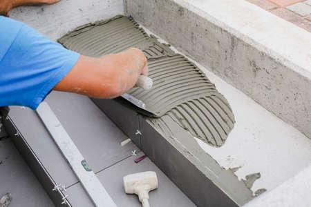 Mani di piastrellista che lavorano su un nuovo ingresso di casa, tuttofare locale e professionale che applica piastrelle ai gradini.