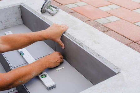 Tiler hands working on a new house entrance, local and professional handyman applying tiles to the steps. Reklamní fotografie - 129975064
