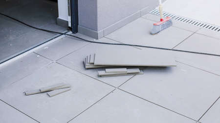 Tiler worling by laying new tiles on a house entrance