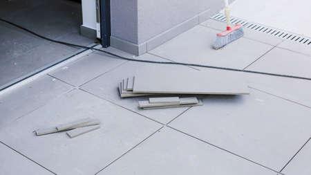 Tiler worling by laying new tiles on a house entrance Reklamní fotografie - 129975066