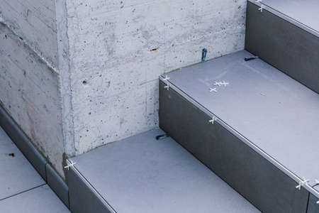 Laying new tiles on a concrete steps outside of a building Reklamní fotografie - 129975069