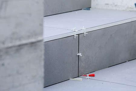 Laying new tiles on a concrete steps outside of a building Фото со стока