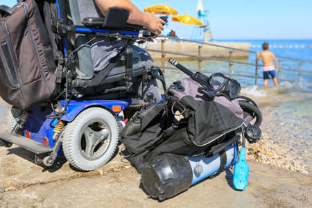 Handicapped disabled scuba diver with equipment on a beach shore looking at sea Stock Photo