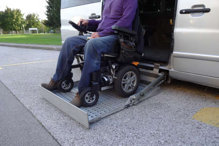 Disabled Men on Wheelchair using Accessible Vehicle with Lift Stock Photo