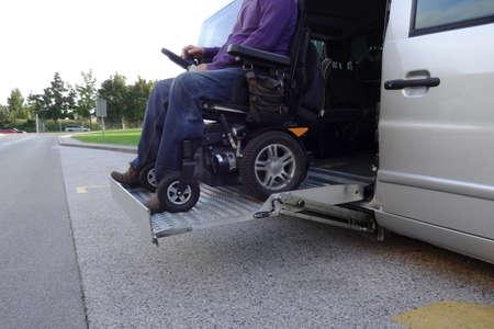 Hommes handicapés en fauteuil roulant utilisant un véhicule accessible avec ascenseur Banque d'images