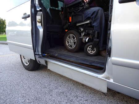 Hombres discapacitados en silla de ruedas que utilizan un vehículo accesible con ascensor