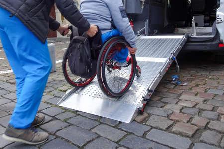 Asistente que ayuda a la persona discapacitada en silla de ruedas con el transporte mediante rampa para furgonetas