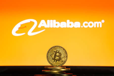 Bitcoin on a stack of coins with Alibaba logo on a laptop screen. Cryptocurrency and blockchain adoption getting mainstream. Slovenia - 02 24 2019