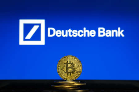 Slovenia, Ljubljana - 02 24 2019: Bitcoin on a stack of coins with Deutsche Bank logo on a laptop screen Reklamní fotografie - 136918868