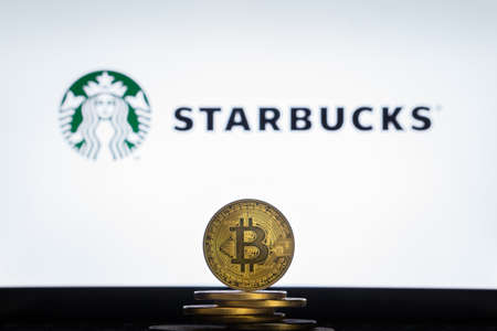 Slovenia, Ljubljana - 02 24 2019: Bitcoin on a stack of coins with Starbucks logo on a laptop screen