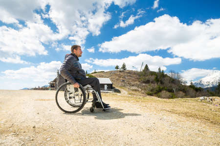 Happy man in wheelchair outside in nature on a sunny summer day in the mountains