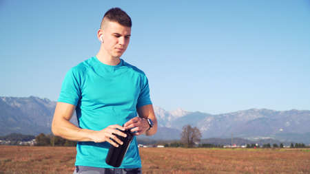 fit young man preparing protein shake and drinking it with mountains the back Reklamní fotografie