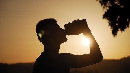 silhouette di un giovane in forma che beve acqua con il sole e la natura dietro al tramonto