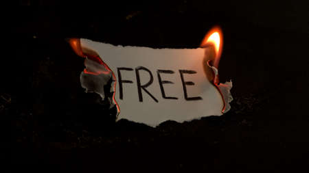 Free word written on white paper burns. Fire with smoke and ashes on black background Reklamní fotografie
