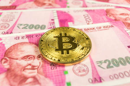 Cryptocurrency gold Bitcoin coin on a Indian rupee Reklamní fotografie