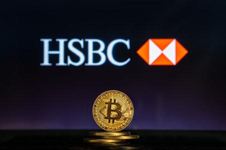 Slovenia, Ljubljana - 02 24 2019: Bitcoin on a stack of coins with HSBC Bank logo on a laptop screen Reklamní fotografie - 136926391