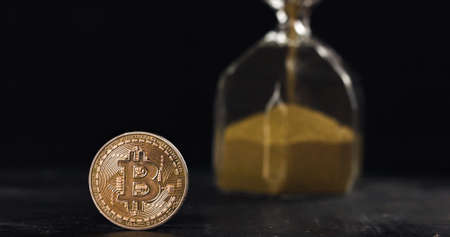 Bitcoin hodl for years and get rich concept, time is running out. Bitcoin coin next to hourglass