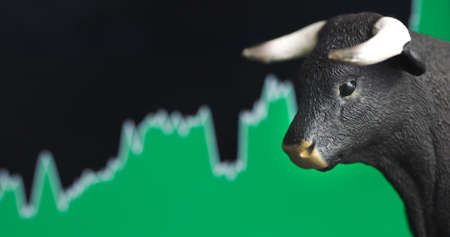 Stock price rise with green chart bullish top in background and bull in front. Market trend concept. Reklamní fotografie