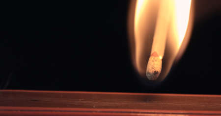Firing up matches. Ignition lose-up detail of on matchbox and showing burning flame